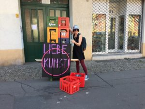 Nicole standing next to 12 beer boxes which are attached to a skateboard. The LIEBE. KUNST! sign and a hula hoop are also attached to the skateboard.