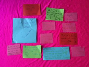 A series of notes written on coloured construction paper by the art installation's participants describing what Ridiculous Love means to them. The background is the same vibrant pink as the installation piece.